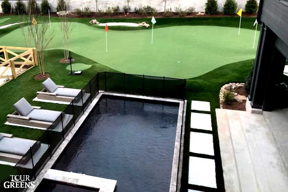 Tour Greens putting green doubling as a pool surround in the backyard