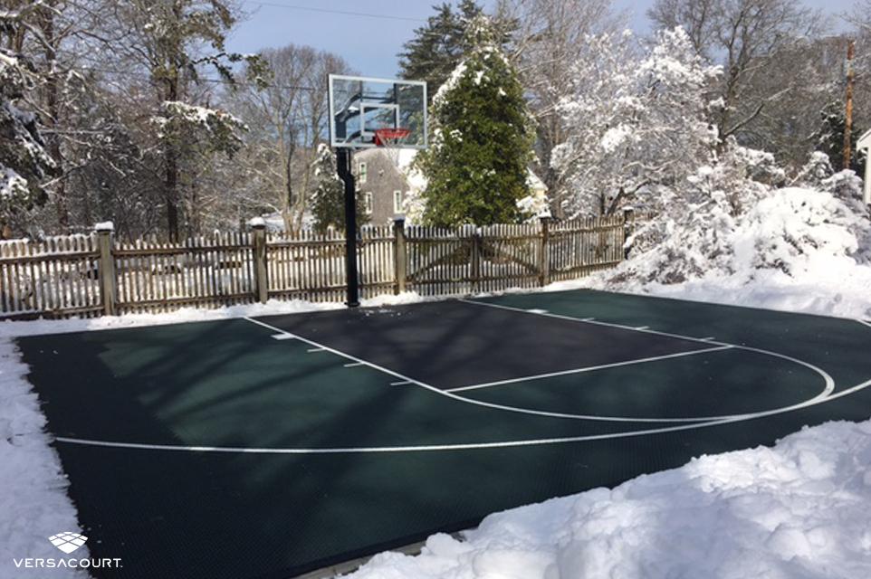 VersaCourt backyard basketball court during the winter