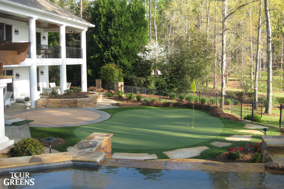 Pool, patio, and putting green installed in a large backyard