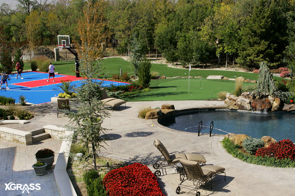 Elegant backyard with a basketball court from VersaCourt and a putting green from TourGreens