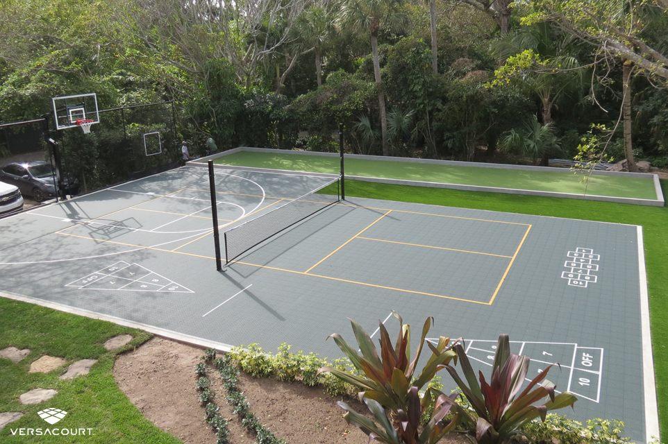Backyard installed with a multi-sport game court featuring basketball, pickleball, volleyball, shuffleboard, and hopscotch