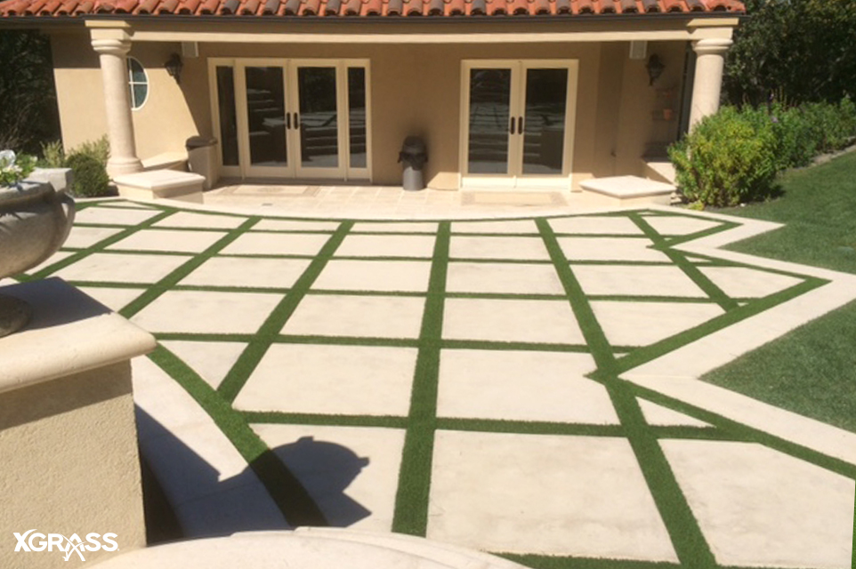 Artificial turf strips installed on paver patios in the backyard