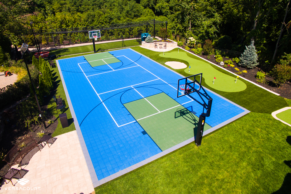 Backyard with a multi sport game court, a batting cage, and putting green