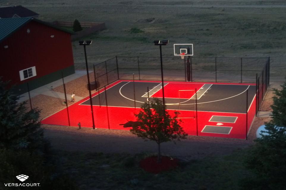 Backyard basketball court with court lighting