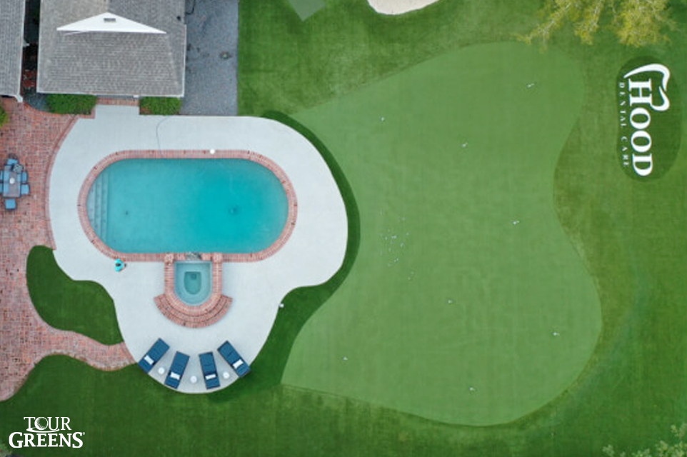Large backyard swimming pool with a novelty putting green from Tour Greens installed