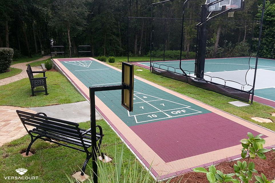 Backyard installed with a shuffleboard court, half-court basketball court, and ball rebounder