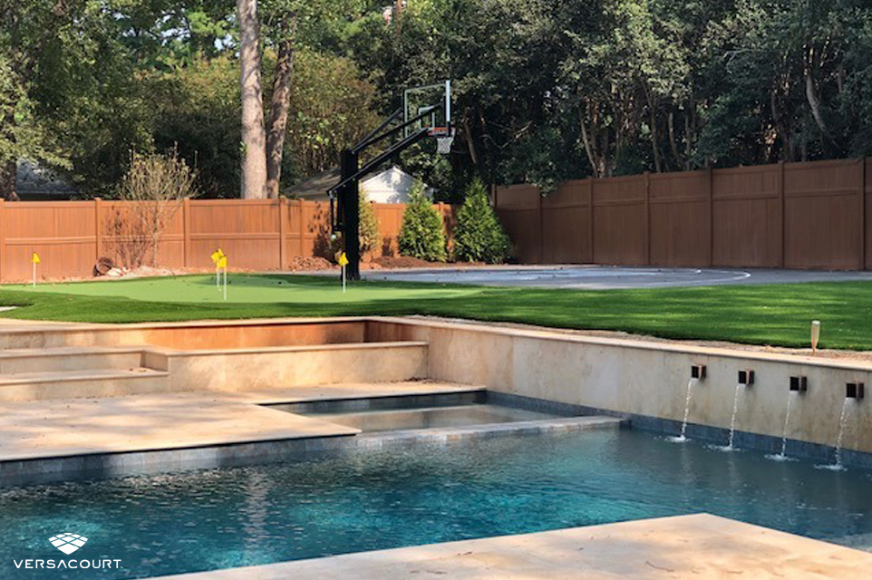 Backyard swimming pool with a putting green and basketball court next to it