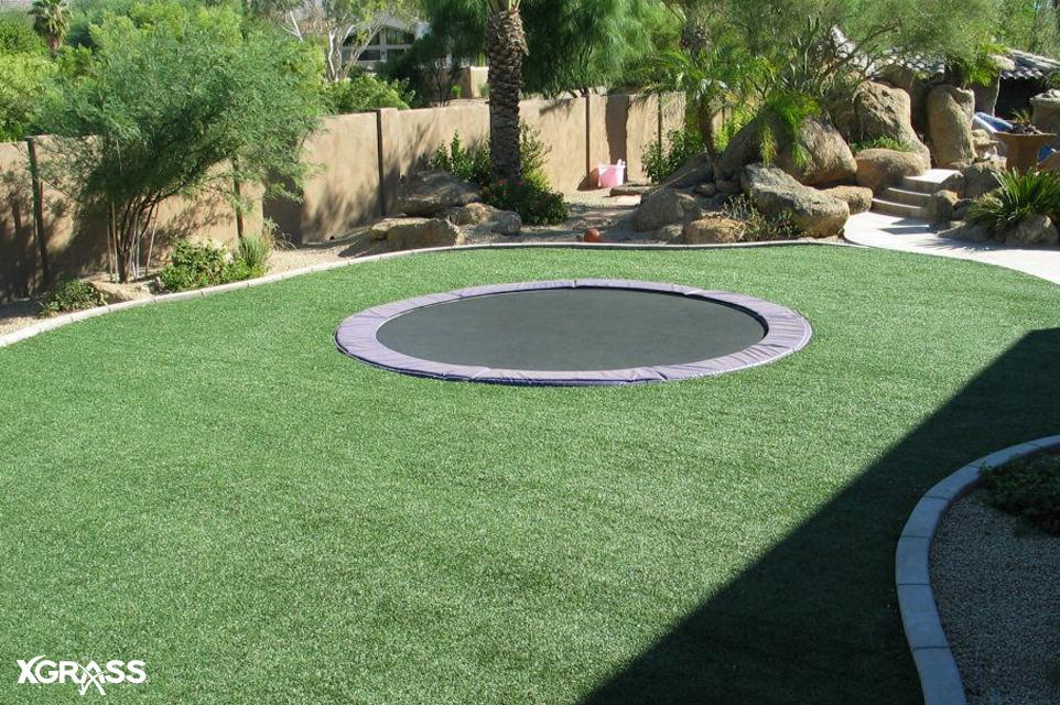 In-ground trampoline with XGrass artificial grass installed around it