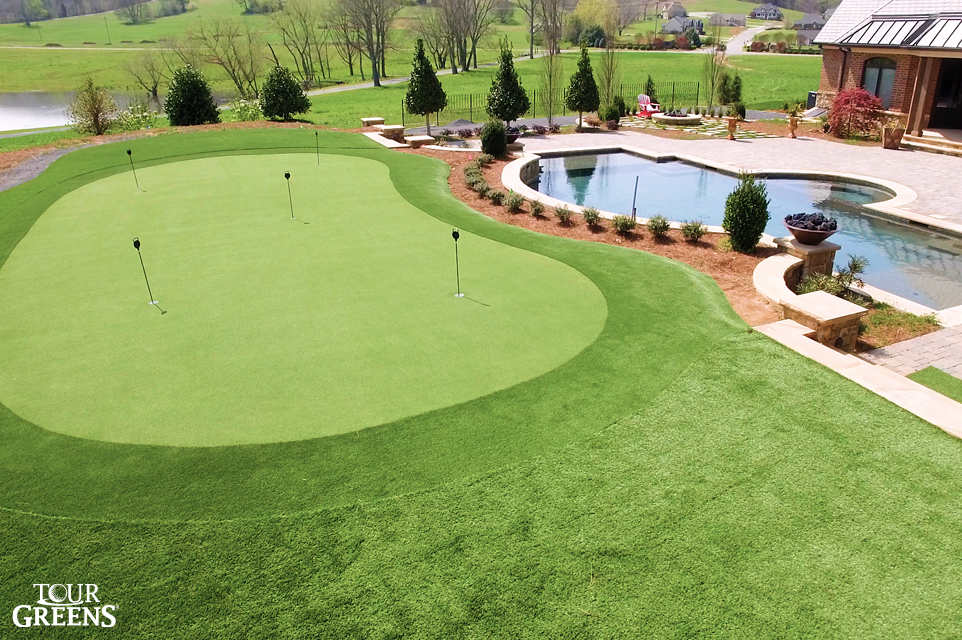 Large backyard installed with a large putting green area by a swimming pool
