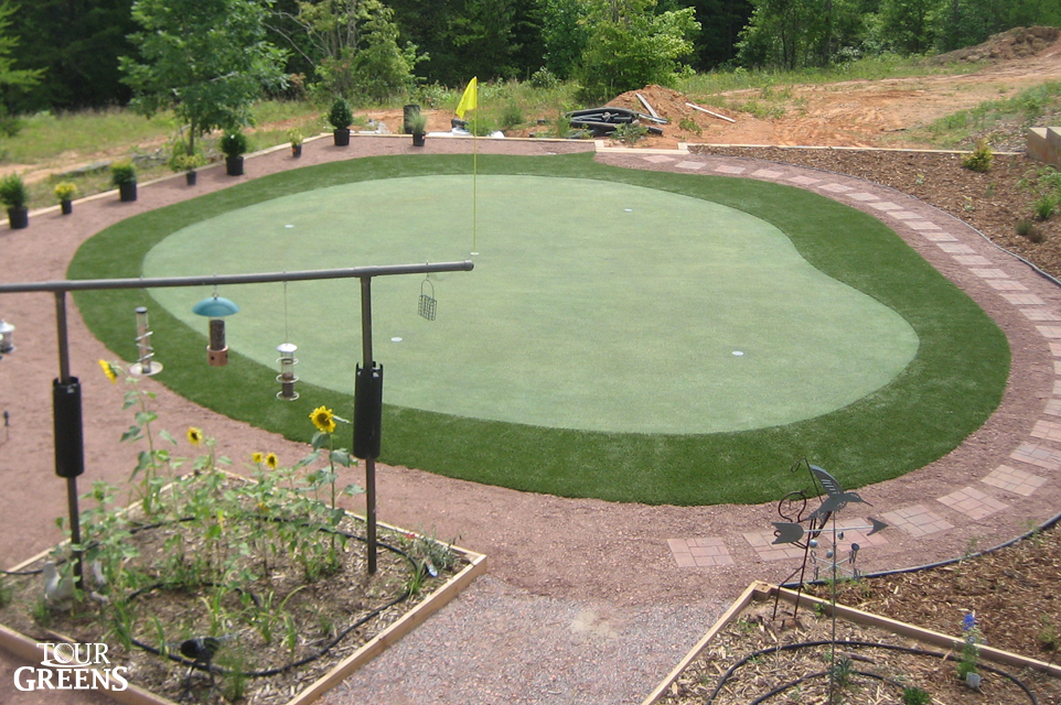 Backyard patio with a small putting green installed