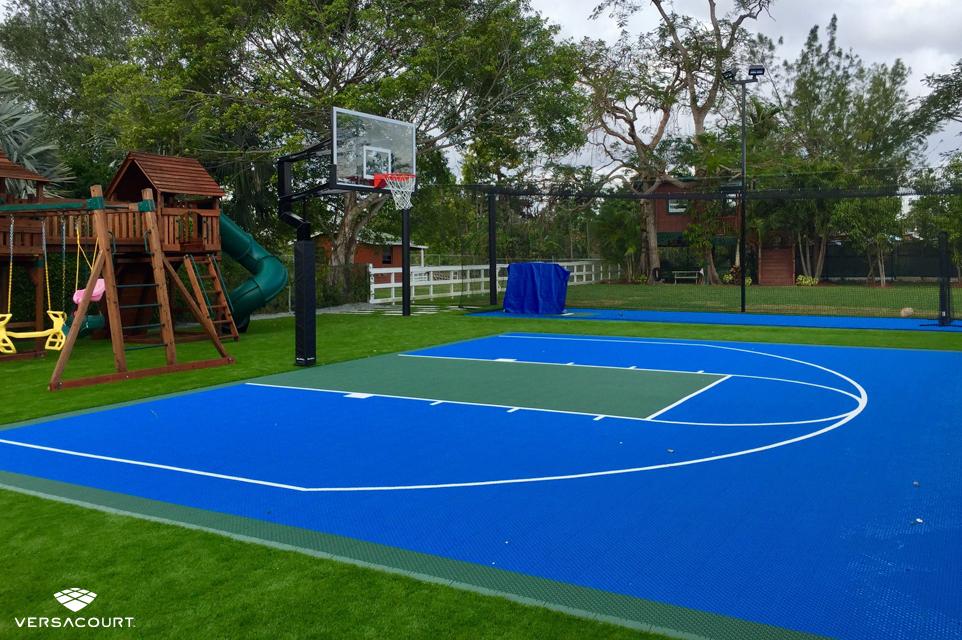 Backyard playground with VersaCourt's basketball court installed