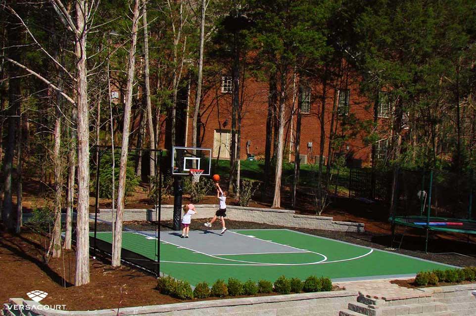 Kids playing in their backyard basketball court
