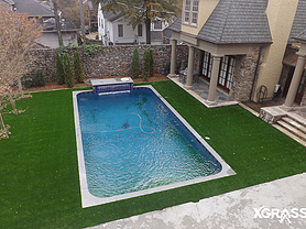 Top view of swimming pool surrounded by artificial turf