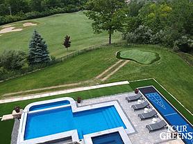 Tour Greens backyard putting green next to swimming pool